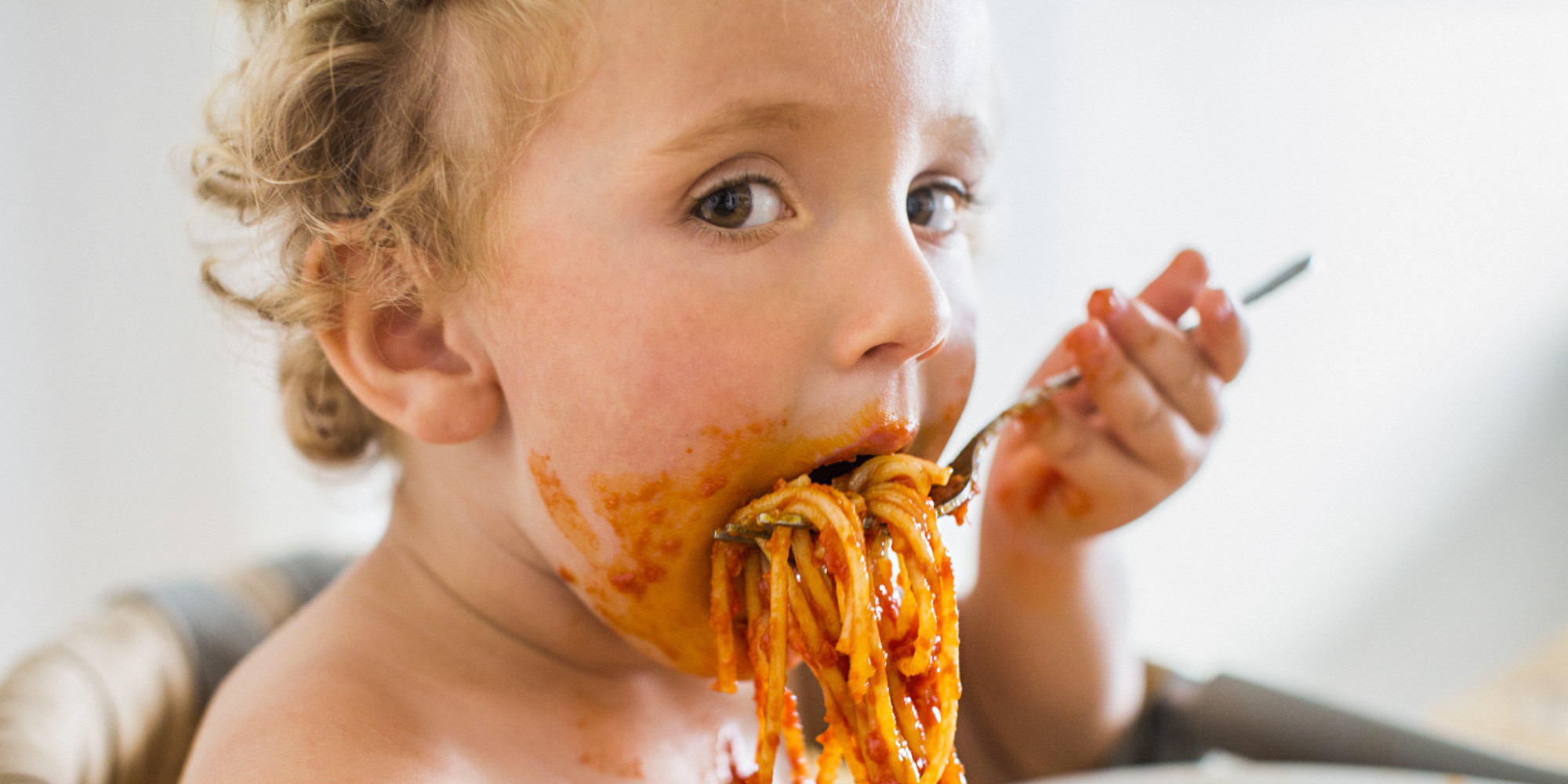 Young toddler boy eating messy pasta
