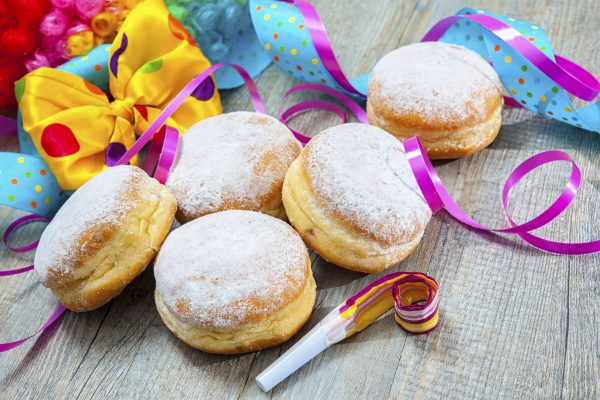 Krapfen or jelly doughnuts with jam and icing sugar