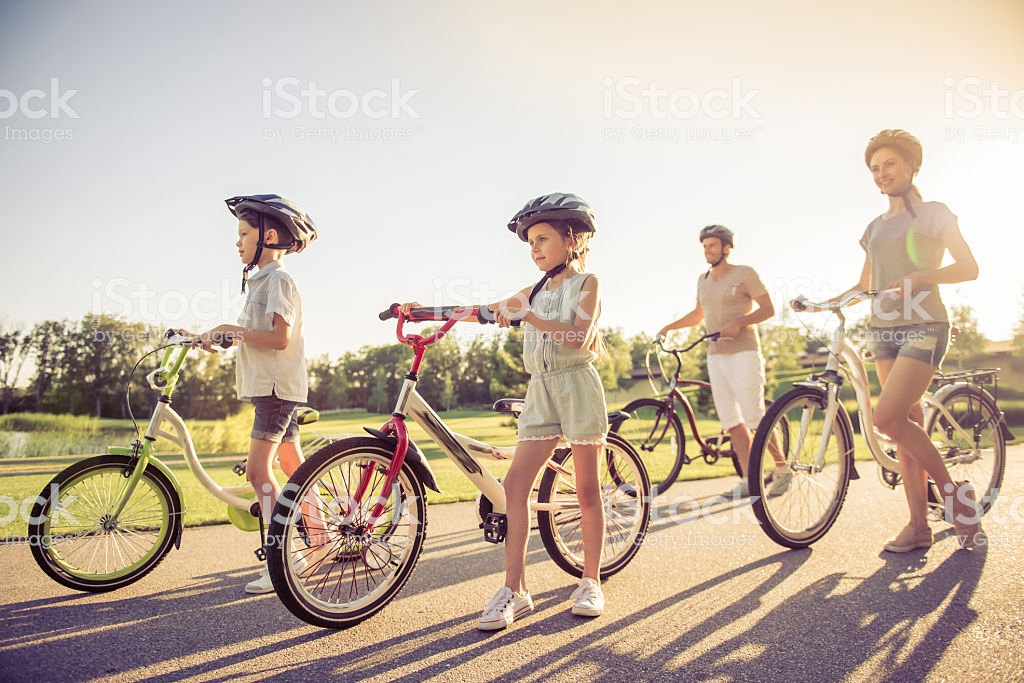 Happy family is riding bikes outdoors and smiling, full length
