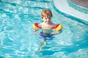 Happy little kid boy having fun in an swimming pool. Active happy preschool child learning to swim. with safe floaties or swimmies. Family, vacations, summer concept.