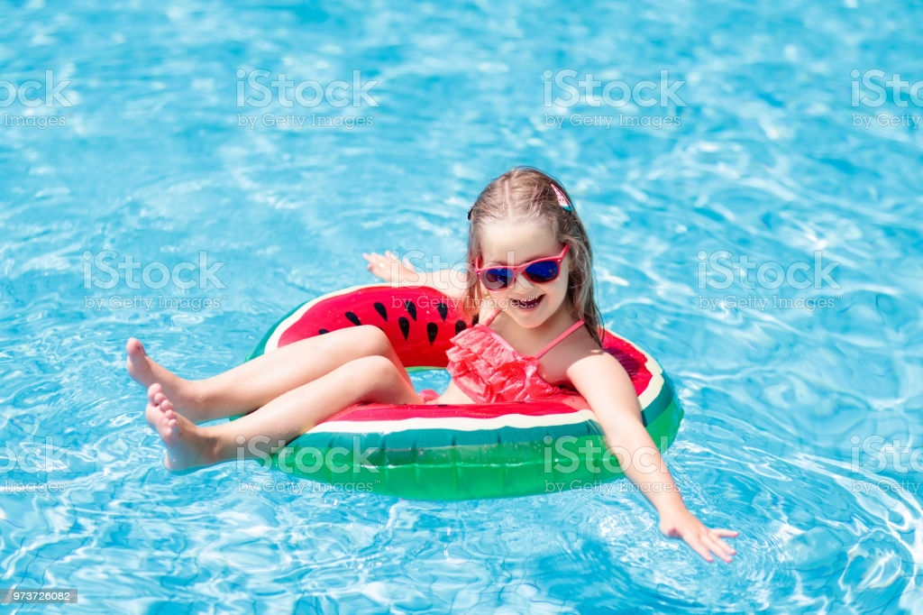 Child with watermelon inflatable ring in swimming pool. Little girl learning to swim in outdoor pool of tropical resort. Kid eye wear. Water toys and floats for kids. Healthy sport for children.